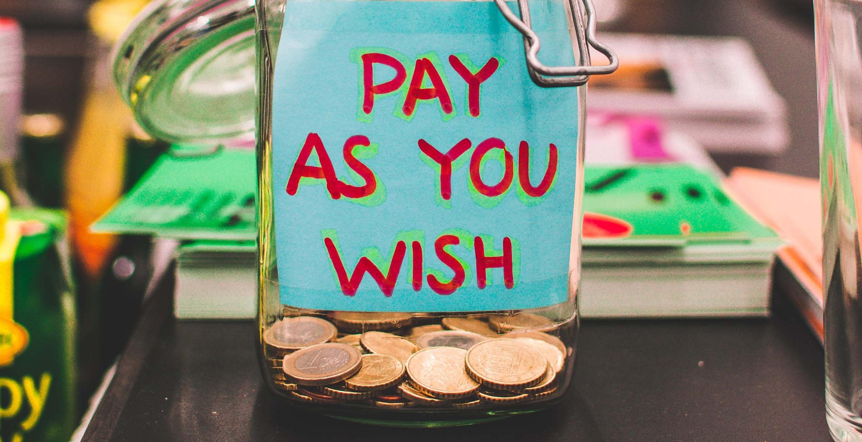 Geldpot met een papiertje waar 'pay as you wish' op staat