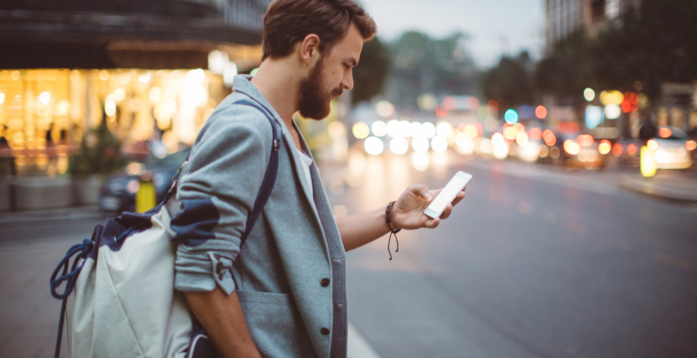 Man met rugtas kijkt op zijn smartphone